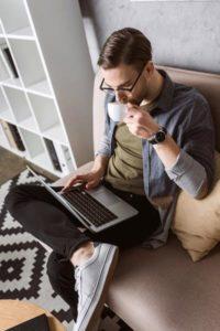 Mann arbeitet mit Laptop auf einer Couch - Homeoffice