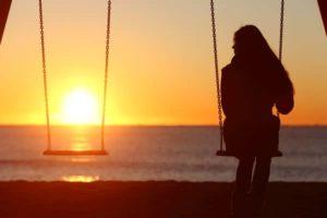 Frau sitzt einsam auf Schaukel